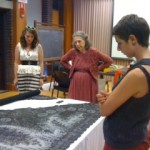 Historic Dress scholar Nancy Rexford (center) instructs students on how to examine a lace shawl.
